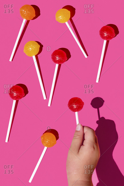 Studio shot of hand of baby girl picking up one of lollipops lying against pink background