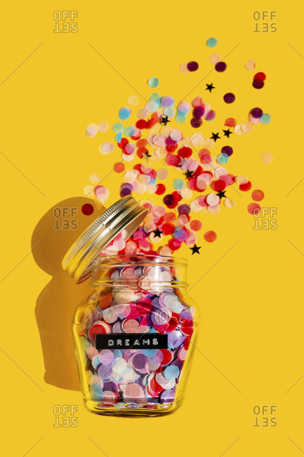 Colorful confetti spilling from glass jar
