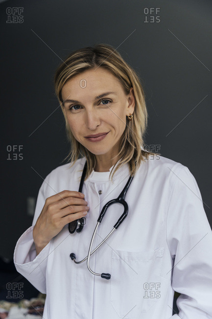 Portrait of doctor with stethoscope against grey background