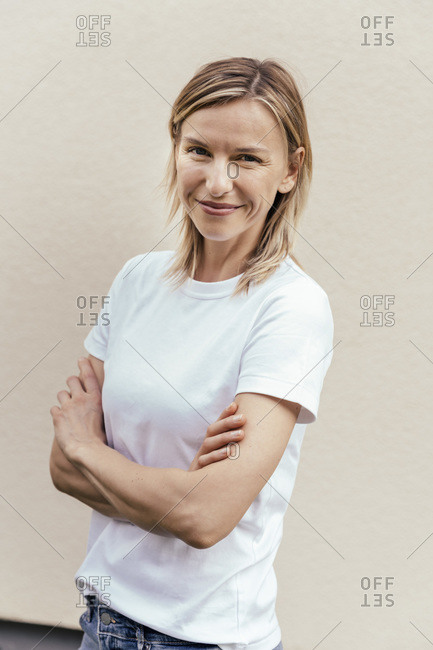 Portrait of smiling blond woman standing in front of light wall