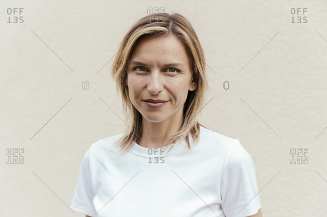 Portrait of smiling blond woman wearing white t-shirt in front of light wall