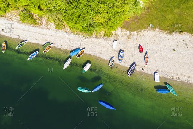 Germany- Bavaria- Lenggries-R owboats left on green shore of Sylvenstein Reservoir