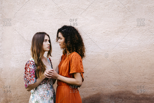 Portrait of two young women holding hands looking at each other