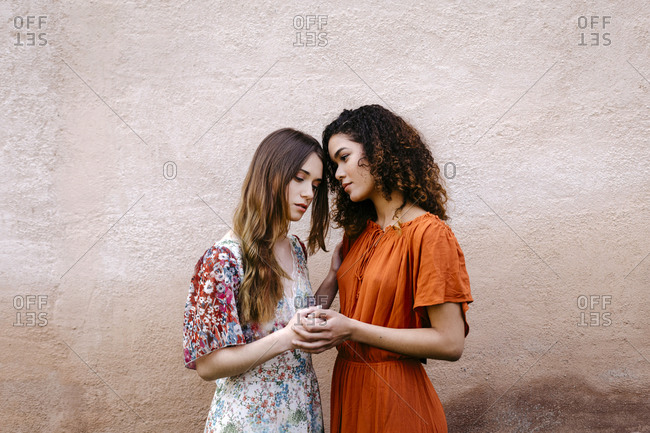 Portrait of two young women holding hands