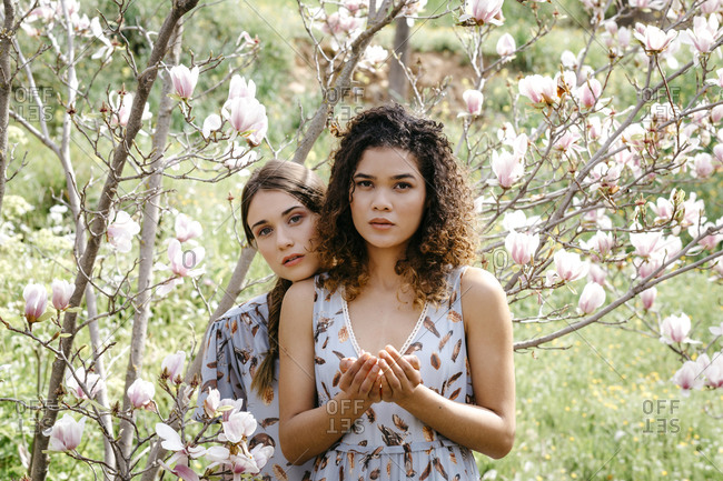 Loving sisters standing amidst flowers in park during springtime