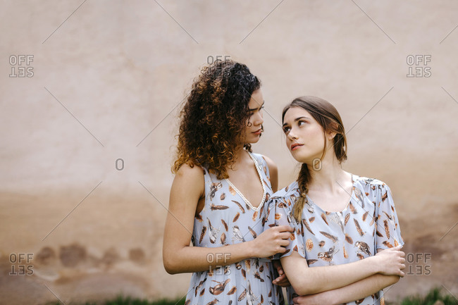 Loving sisters wearing dresses looking at each other while standing against old wall