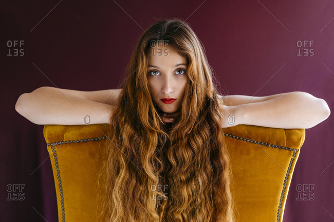 Portrait of young female fashion model with long brown wavy hair leaning on golden chair against colored background