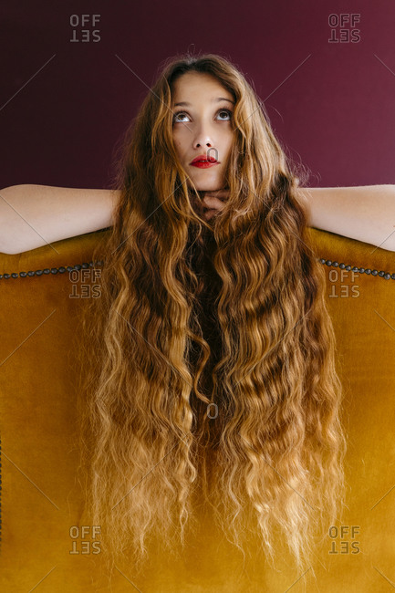 Young female fashion model with long brown wavy hair leaning on golden chair while looking up against colored background