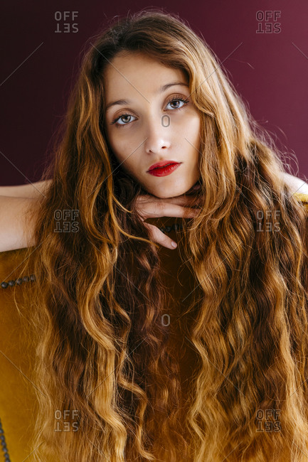 Portrait of young woman with long brown wavy hair leaning on chair against colored background