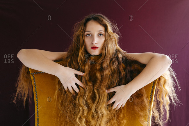 Portrait of confident young woman with long brown wavy hair leaning on chair against colored background