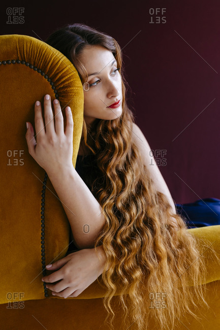 Thoughtful young woman with long brown wavy hair sitting on golden chair against colored background