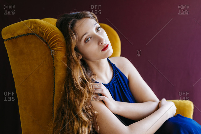 Thoughtful young fashion model with long brown hair looking away while sitting on golden chair against colored background