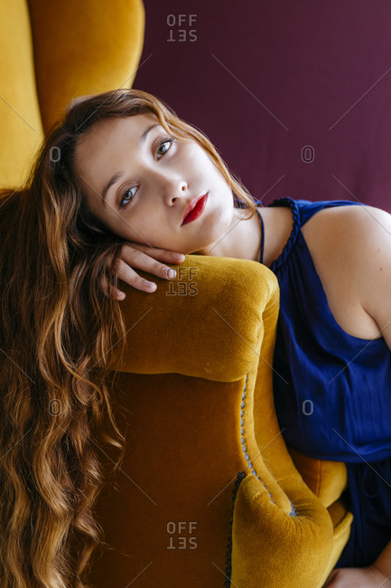 Portrait of confident young woman leaning on golden chair against magenta background