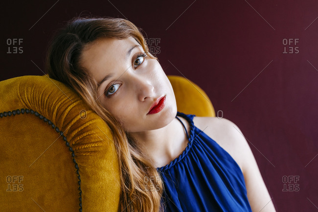 Close-up portrait of confident young woman sitting on golden chair against magenta background
