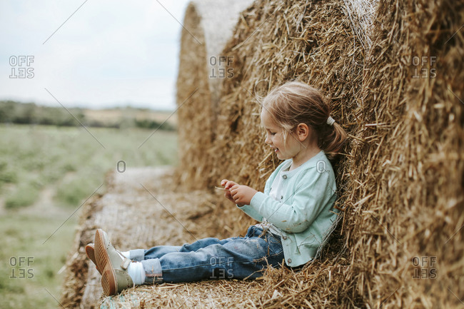 Little girl sitting on straw bales