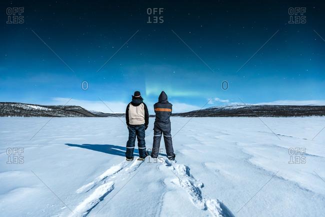 Snowshoe hikers standing in winter landscape watching northern lights above Ropijarvi- Ropinsalmi- Enontekioe- Finland