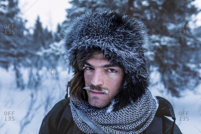 Portrait of man in winter forest with frozen moustache- Ounasjaervi- Enontekioe- Finland