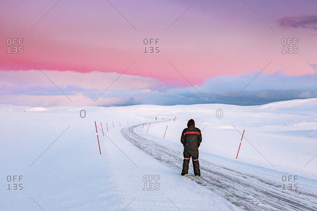 Man standing on road in winter landscape- Tana- Norway