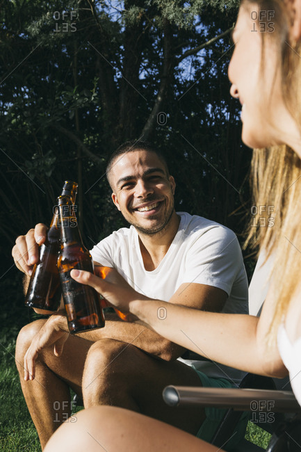 Smiling man toasting beer bottle with girlfriend while sitting at tourist resort