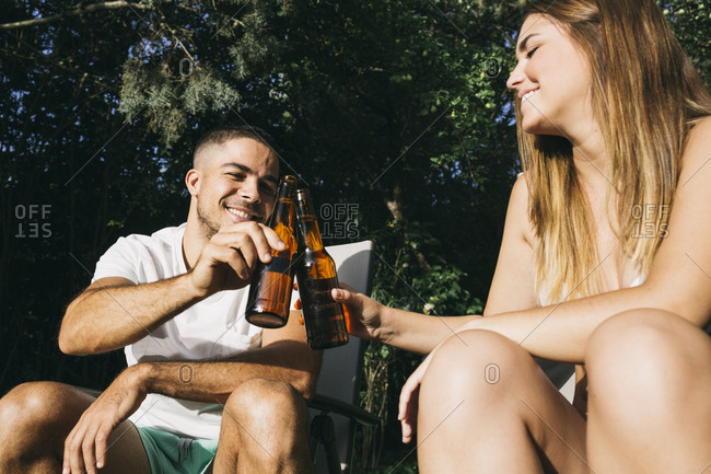Smiling young couple toasting beer bottles while sitting at tourist resort