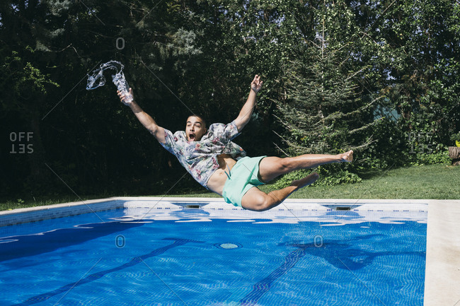 Shocked young man holding drink falling in swimming pool against trees