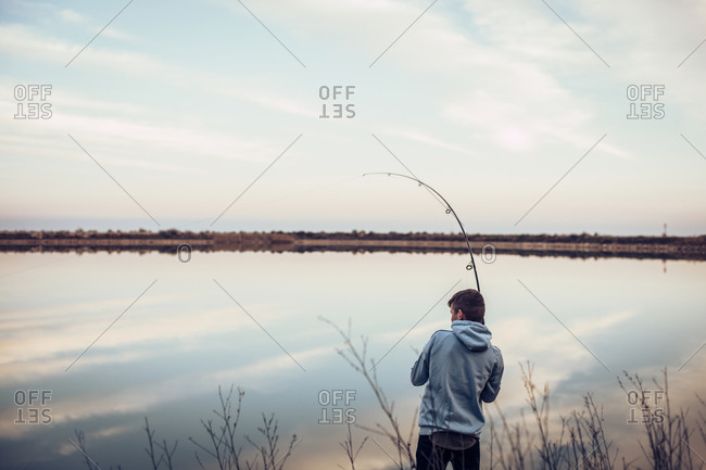 Rear view of teenage boy wearing hooded shirt fishing with rod in lake against cloudy sky