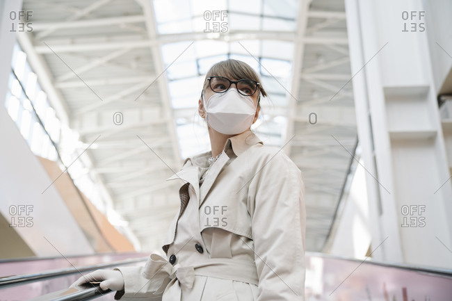Woman with face mask and disposable gloves on an escalator in a shopping center