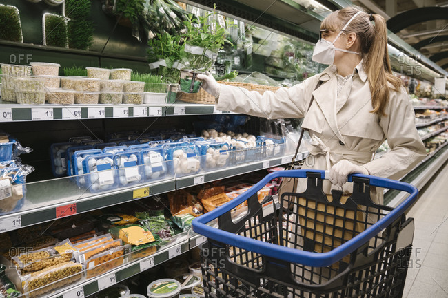 Woman with face mask and disposable gloves in a supermarket