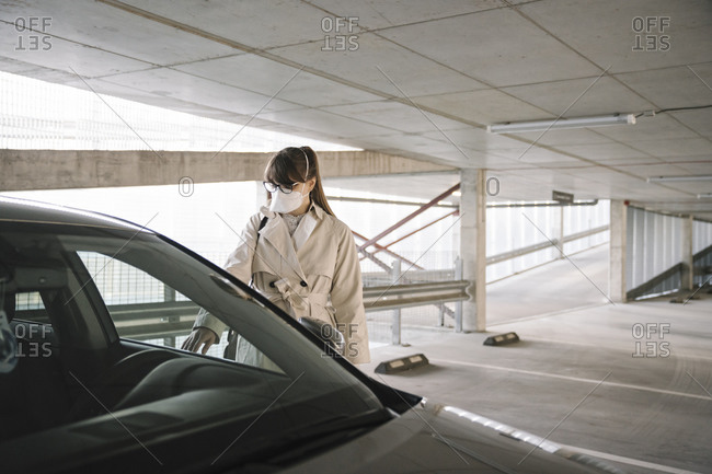 Woman wearing face mask opening car in a car park