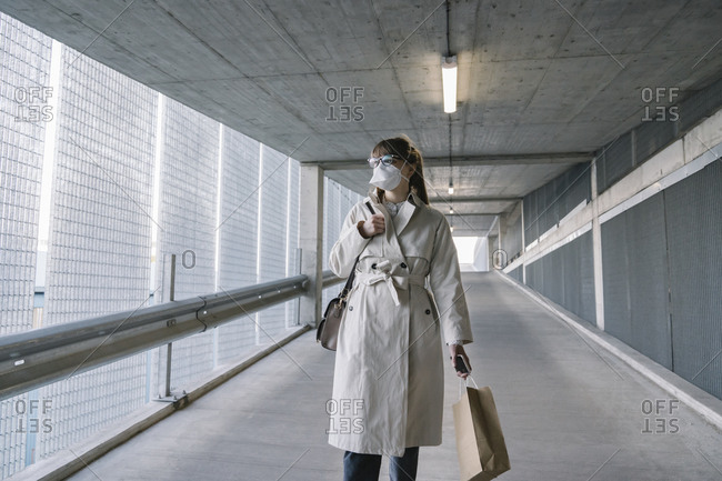 Woman wearing face mask walking in corridor of a car park after shopping