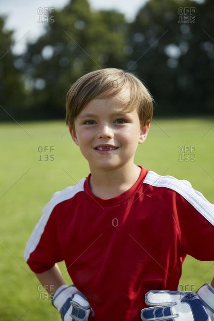 Portrait of happy boy in soccer uniform standing on field