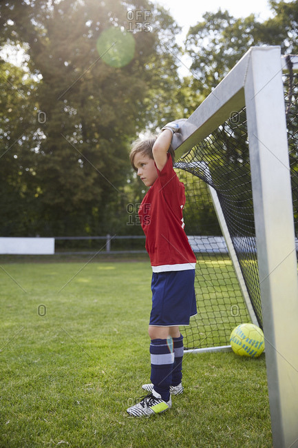 Boy in soccer uniform holding goal post at field