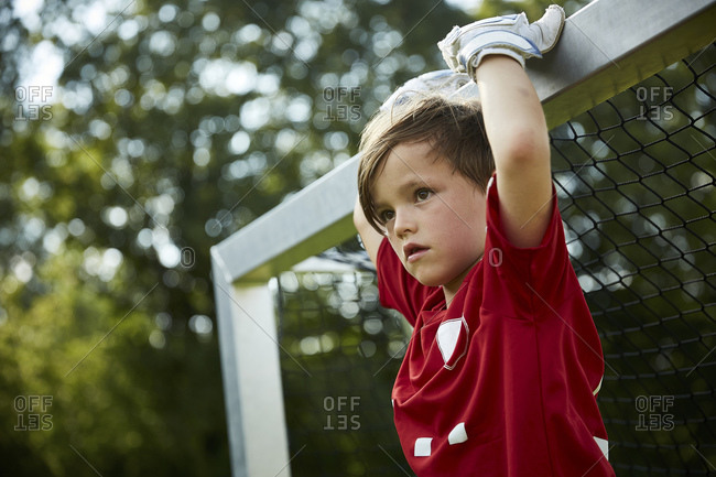 Thoughtful soccer boy holding goal post at field