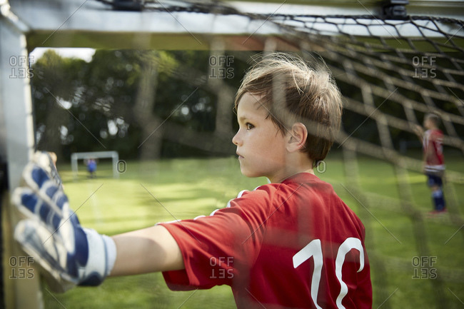 Serious boy in soccer uniform holding goal post at field