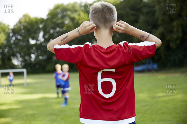 Soccer boy holding ears while standing on field