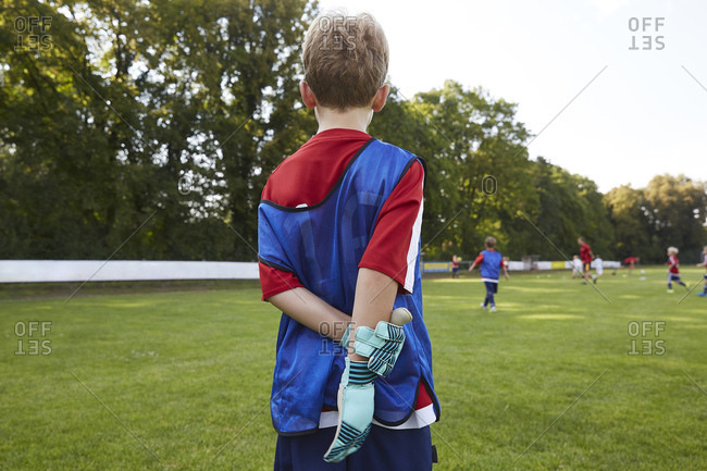 Soccer boy in uniform standing on field