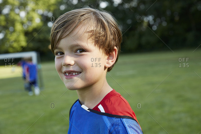 Close-up portrait of happy soccer boy on field