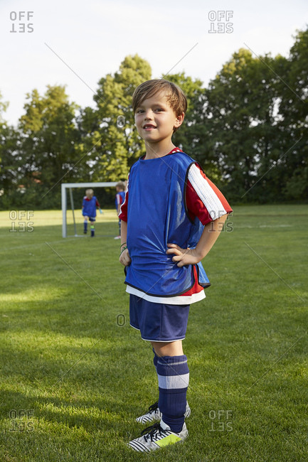 Portrait of confident soccer boy with hands on hips standing on field