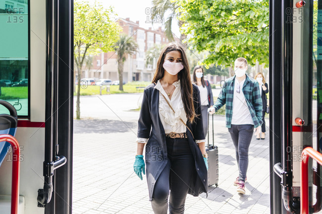 Portrait of young woman wearing protective mask and gloves getting into bus- Spain