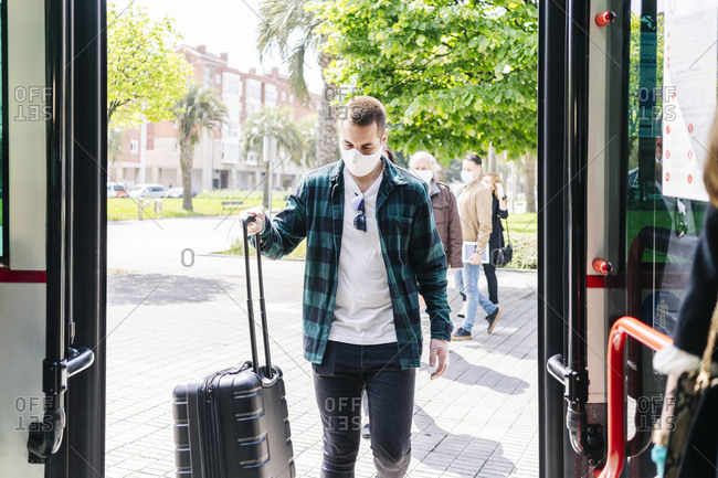 Young man wearing protective mask getting into bus with trolley bag- Spain