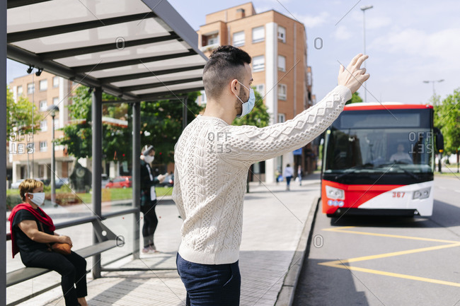 Man wearing protective mask standing at bus stop hailing taxi- Spain