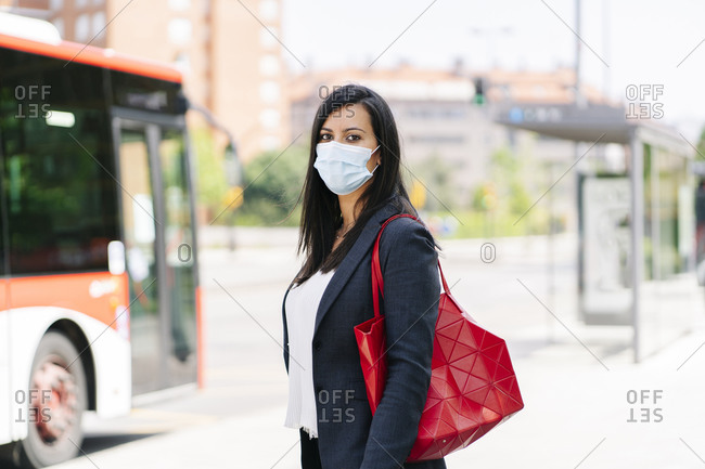 Portrait of woman wearing protective mask waiting at bus stop- Spain