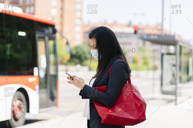 Woman wearing protective mask using smartphone while waiting at bus stop- Spain