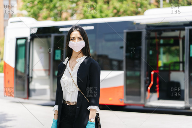 Portrait of young woman wearing protective mask and gloves waiting at bus stop- Spain
