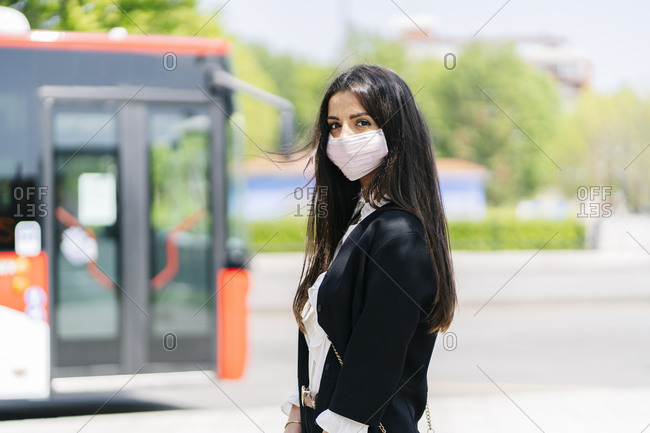Portrait of young woman wearing protective mask waiting at bus stop- Spain