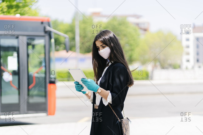 Young woman wearing protective mask and gloves using digital tablet while waiting at bus stop- Spain