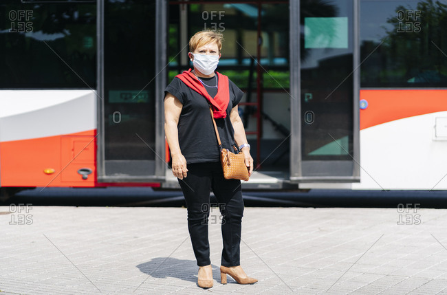 Portrait of mature woman wearing protective mask waiting at bus stop- Spain