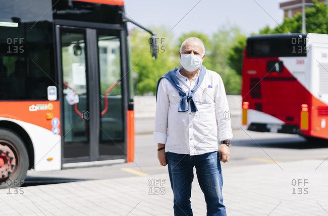 Portrait of mature man wearing protective mask waiting at bus stop- Spain
