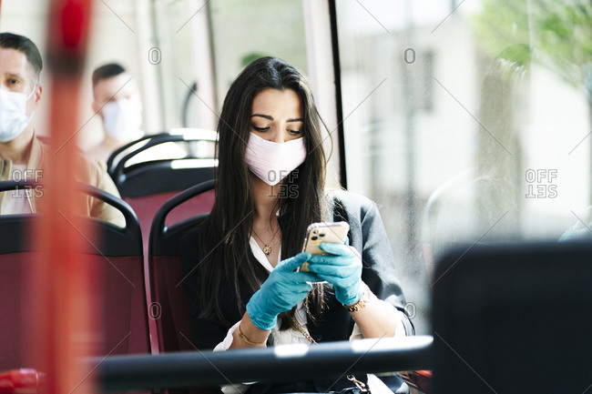 Portrait of young woman wearing protective mask in bus looking at cell phone- Spain