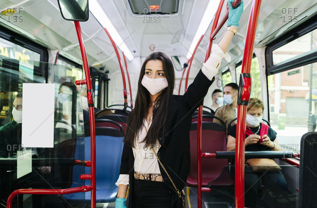 Portrait of young woman wearing protective mask and gloves in public bus- Spain